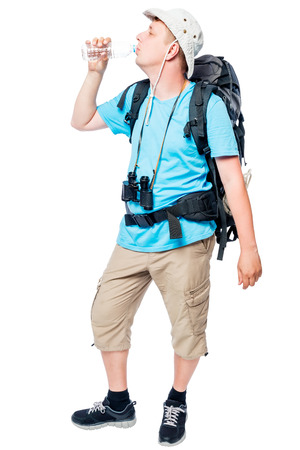 Hiker with a backpack eagerly drinks water from a bottle on a white background