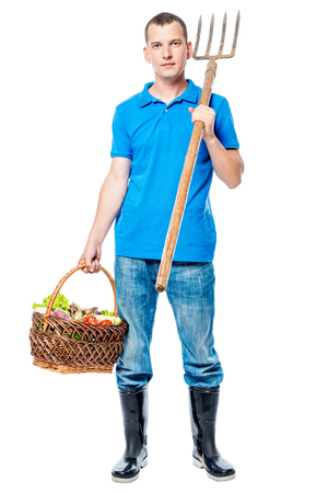 Full length portrait of a farmer with a pitchfork and a basket of vegetables isolated Stockfoto