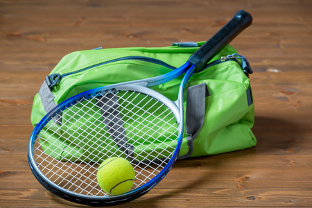 haversack: Green sports bag and a racket for a game of tennis close-up on the floor
