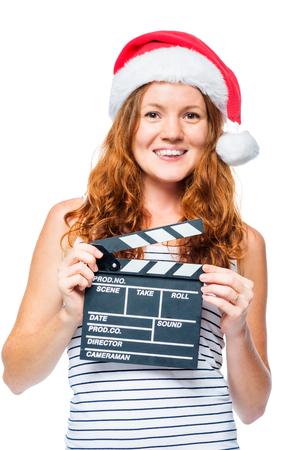 Mooi meisje in een kerstmuts met een film klapper op een witte achtergrond Stockfoto