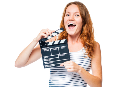audition: joyful girl on a white background with a movie clapper in the studio