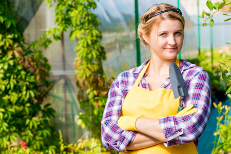 Beautiful young girl working in a greenhouse gardener Stock Photo