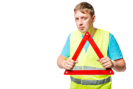 Man in a vest holds in his hands an emergency stop sign on a white background