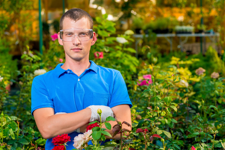Man in glasses and laboratory gloves in a greenhouse among flowers