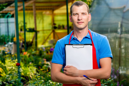 Horizontal portrait of a businessman in a greenhouse with a blank in his hands