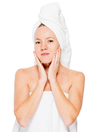 moisturize: Young girl in a towel after a shower touches her face skin isolated Stock Photo