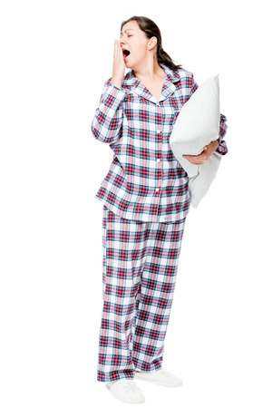 Beautiful brunette wants to sleep, yawns, dressed in pajamas holds a pillow on white background