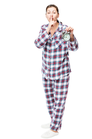 drowsy: Girl with an alarm clock in checkered pajamas showing a gesture quieter on a white background Stock Photo
