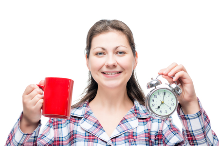 drowsy: Morning portrait of a beautiful girl with a cup of coffee and an alarm clock on a white background
