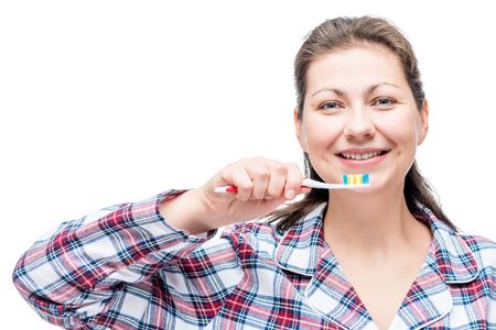 pasta de dientes: Alegre niña en pijama con un cepillo de dientes en la mañana, retrato sobre un fondo blanco