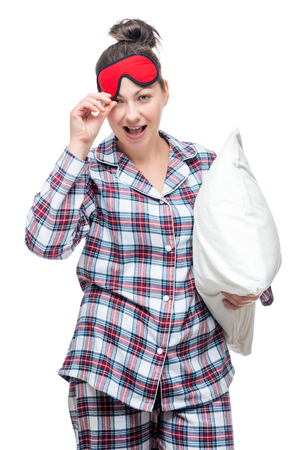 Beautiful cheerful woman in pajamas and a mask for sleep holds a pillow on a white background Stock Photo