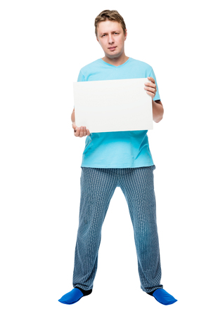 Man in pajamas on a white background holds a placard for inscription Stock Photo