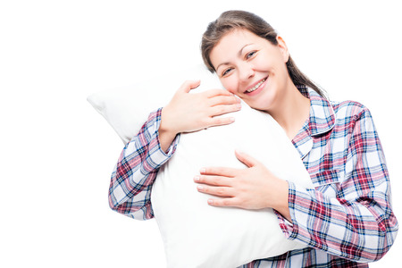 Happy brunette in pajama hugs soft pillow against white background