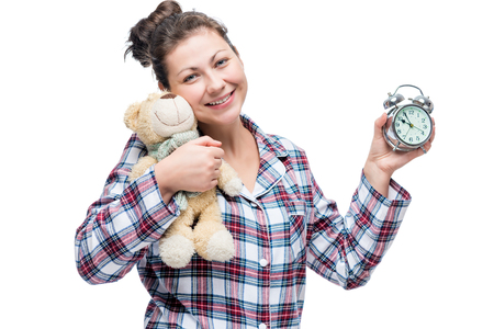 Beautiful smiling girl in plaid pajamas with a bead and toy isolated