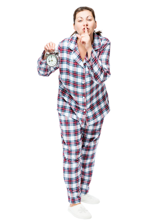 Young woman with an alarm clock in checkered pajamas showing a gesture quieter on a white background
