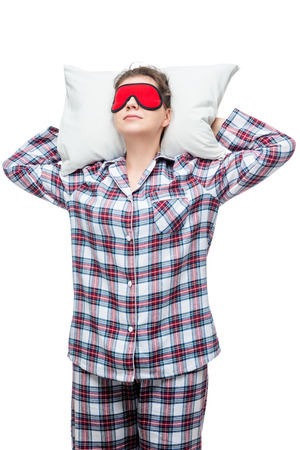 Sleeping woman on a pillow in plaid pajamas with a mask in front of her eyes isolated
