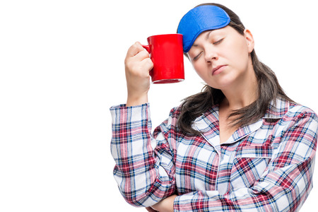 Girl with a mug of coffee trying to wake up and cheer up in the morning on a white background