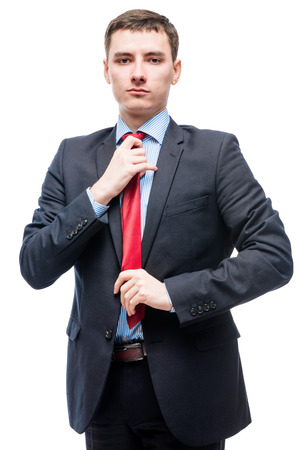 corrects: Man in suit corrects red tie, portrait on a white background Stock Photo