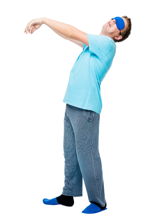 Man suffers from sleepwalking, portrait in pajamas on white background Stock Photo