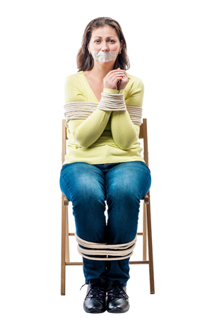 Connected young hostage in a chair on a white background Foto de archivo