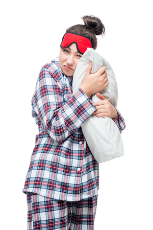 Sleepy woman in pajamas hugging her favorite pillow against white background