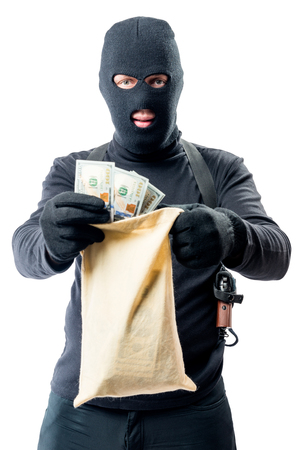 loot: Male robber in full length is holding bag with money on white background