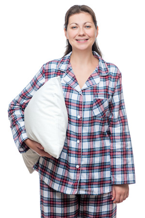 Smiling young woman in pajama with pillow posing on white background