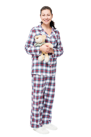 Woman in pajamas with teddy bear on white background in full length Stock Photo