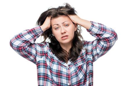 headaches: Sleepy unhappy woman in pajamas on a white background isolated Stock Photo