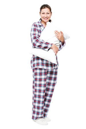 Girl with a pillow in full length on a white background, dressed in pajamas and slippers Stock Photo