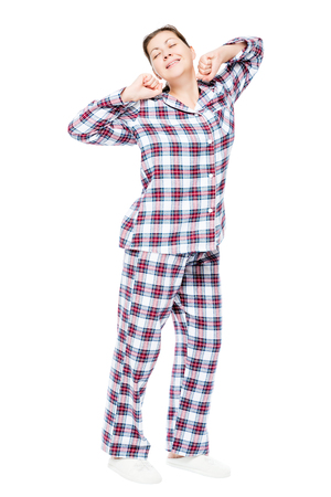 woken up girl in pajamas stretching on a white background, full length portrait Stock Photo