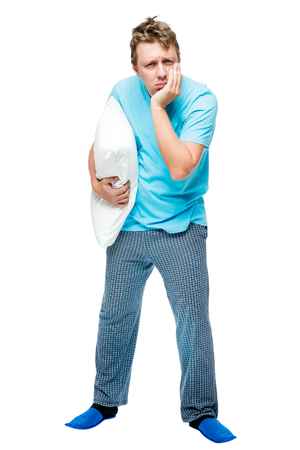somnambulism: Sleepy man in pajamas with a pillow in his hand on a white background