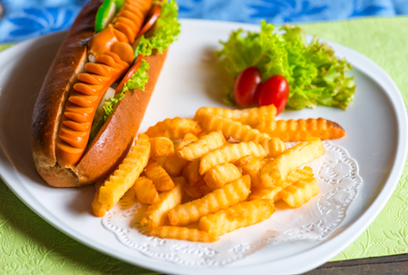Fast food is nicely served on a plate hot dog and potatoes with vegetables