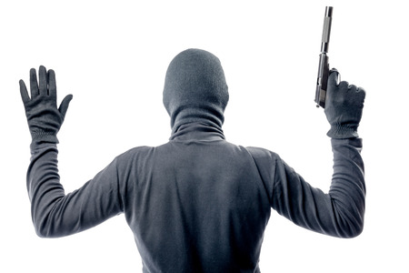Criminal with a pistol in a balaclava raised his hands up with a gun