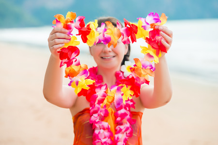 Girl on the beach welcomes guests with floral Lei traditional Hawaiian Stok Fotoğraf