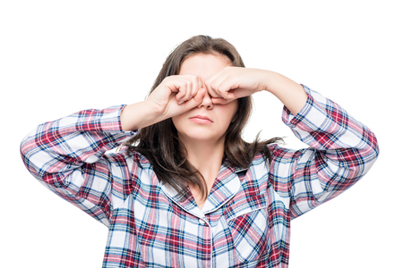sleeping woman in pajamas rubbing his eyes with his hands on a white background Stock Photo