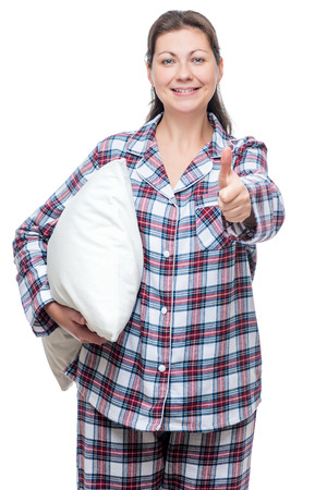 Satisfied young woman in pajama with pillow posing on white background