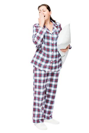 Yawning sleepy woman in warm pajamas holds ready pillow on white background isolated Stock Photo