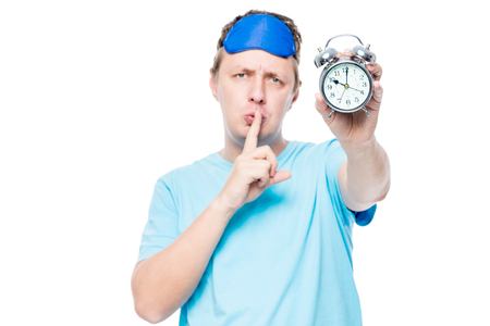 Portrait of a man with an alarm clock showing a gesture of a finger near the lips, says you need to be quieter