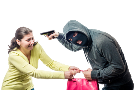 Street thief in a balaclava with a gun steals a womans bag, shooting on a white background