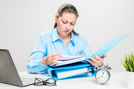 The financial analyst carefully examines the companys documents at the desk in the office Stock Photo