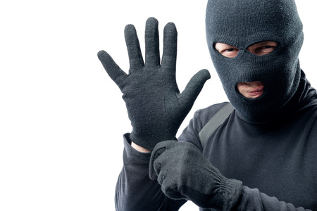 The criminal puts on a glove. Preparation for robbery 版權商用圖片