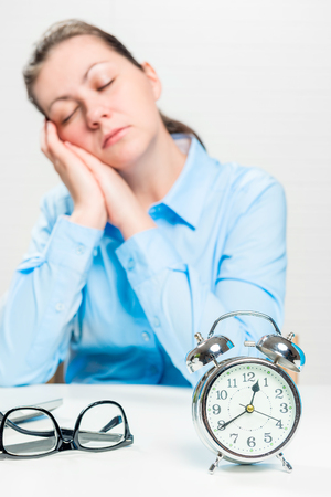 Conceptual picture of a asleep woman in the middle of a working day