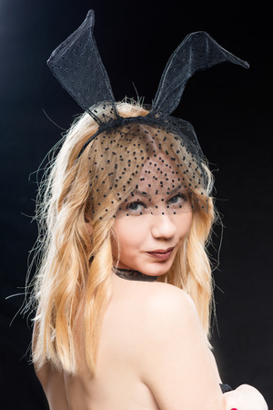 Portrait of sexy woman with bare back in a mask and with rabbit ears on a black background