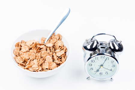 useful breakfast of cereal and alarm clock on white table close-up