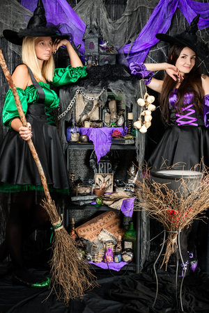smiling young witches with broomsticks and potions cauldron
