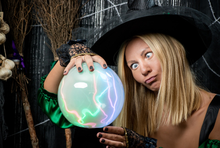 emotional witch looks into a magic ball