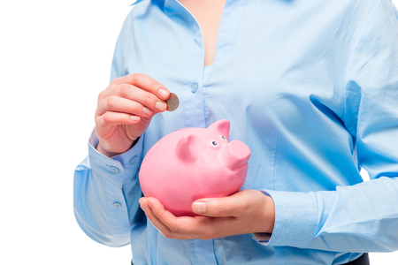 Female hands close-up of a coin in a pink piggy bank Stock Photo