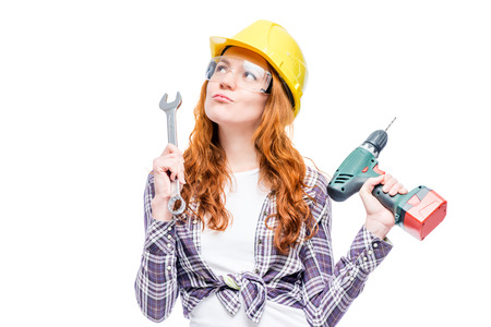 pensive woman carpenter in helmet on white background with tools Stock Photo