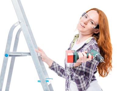 housewife during repairs, portrait on a ladder with tools isolated Stock Photo